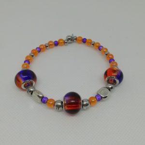 Bracelet en acier inoxydable, fermeture par clip avec boule de sureté. 7 cm de diamètre. Trois perles verre 925 bicolores, perles en acrylique et apprêts en acier inoxydable.