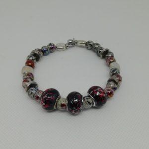 Bracelet en acier inoxydable, fermeture par clip avec boule de sureté. 7 cm de diamètre. Trois perles en acrylique, perles en acrylique et apprêts en acier inoxydable.