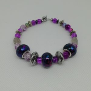 Bracelet en acier inoxydable, fermeture par clip avec boule de sureté. 7 cm de diamètre. Trois perles en acrylique, deux petits disques en hématite, perles en acrylique et apprêts en acier inoxydable.