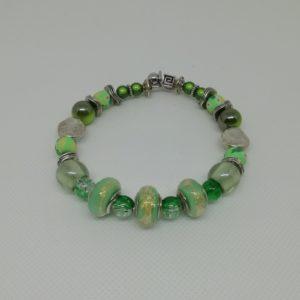 """Bracelet en acier inoxydable, fermeture par clip avec boule de sureté. 7 cm de diamètre. Trois perles verre liséré doré, deux perles verre """"Magic Flair"""", quatre perles Fimo, perles en acrylique et apprêts en acier inoxydable."""
