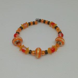 Bracelet en acier inoxydable, fermeture par clip avec boule de sureté. 7 cm de diamètre. Trois perles verre liséré doré, huit perles verre fleur, perles en acrylique et apprêts en bronze antique.