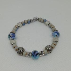 Bracelet en acier inoxydable, fermeture par clip avec boule de sureté. 7 cm de diamètre. Trois perles verre à facettes , perles en céramique et apprêts en acier inoxydable.