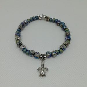 Bracelet en acier inoxydable, fermeture par clip avec boule de sureté. 7 cm de diamètre. Perles en acrylique apprêts et petit pendentif tortue en acier inoxydable.