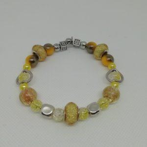 Bracelet en acier inoxydable, fermeture par clip avec boule de sureté. 7 cm de diamètre. Trois perles en acrylique pailletées, deux perles verre et brisures dorées, perles en acrylique et apprêts en acier inoxydable.