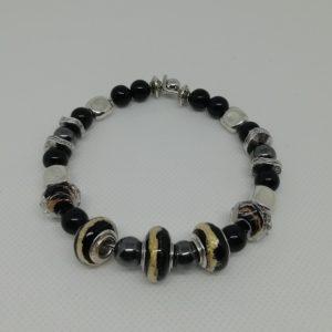 Bracelet en acier inoxydable, fermeture par clip avec boule de sureté. 7 cm de diamètre. Trois perles verre liséré doré, deux perles verre à facettes liséré doré, quatre perles hématite, perles en acrylique et apprêts en acier inoxydable.
