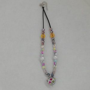 Collier de 43 cm + 4 cm d'extension en suédine noire.Cage cœur en acier inoxydable renfermant des perles multicolores en acrylique. 30 perles en acrylique, 4 apprêts en acier inoxydable.