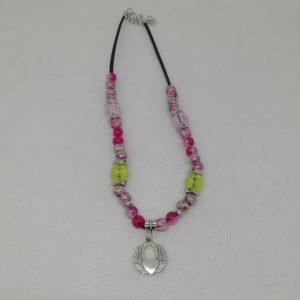 Collier de 43 cm + 4 cm d'extension en suédine noire. Pendentif cœur en acier inoxydable ainsi que deux petits anneaux. 38 perles en acrylique.