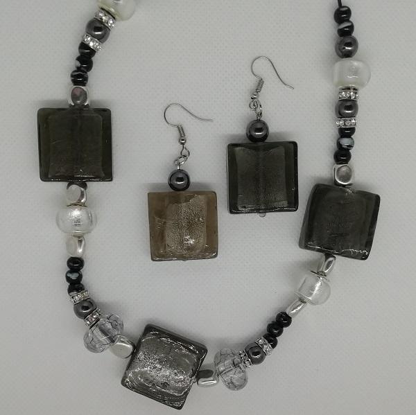 Collier de 55 cm en coton noir ciré et chaînette d'extension de 5 cm. 5 Perles carrées en verre gris. 16 Perles en céramique noires marbrées blanc. 4 Perles en verre argenté brillant. 8 Hématites 2 Perles en acrylique gris transparent. 8 Perles strass 8 Charms en acier inoxydable.