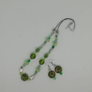 Collier de 50 cm en fil de coton noir ciré et chaînette d'extension de 5 cm. 3 Perles en verre rondes plates avec effet tourbillon blanc et paillettes dorées. 2 Perles rondes en verre vert et éclats de sable doré. 8 Pastilles carrées en verre, vert transparent. 2 Perles en verre givré vert avec feuille ergentée à l'intérieur. 4 Perles en verre vert d'eau et liseré or. 8 Perles bicolores vert/blanc transparent en acrylique cristallisé. 12 Perles en céramiques bicolores vert/marron clair. 12 Charms en acier inoxydable.
