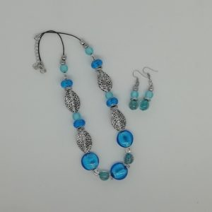 Collier de 50 cm en coton noir ciré et chaînette d'extension 5 cm. 3 Perles rondes plates en verre, couleur bleu avec feuille d'argent à l'intérieur. 4 Perles rondes en verre bleu, éclats de sable doré. 4 Perles en acrylique strié bleu. 6 Perles en verre givré bleu. 4 Feuilles ondulées en métal couleur argent antique. 34 Charms en acier inoxydable.