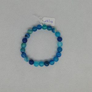 Bracelet composé d'un élastique doublé et agrémenté de perles Agate teintées bleu de 8 mm. Grade AAA. Tour de poignet de 17 à 19 cm.